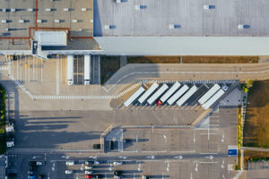 Aerial view of white trailers on semi-trucks parked next to a warehouse