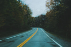 A long stretch of wet, empty road with rain on the windshield